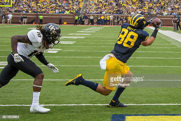 Tight end Jake Butt of the Michigan Wolverines scores a touchdown in the second quarter in front of defensive back Shaquill Griffin of the UCF...