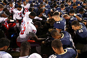 Tight end Jeremiah Gaines of the Southern Methodist Mustangs linebacker Tyler Goble of the Navy Midshipmen and other players join hands in prayer...