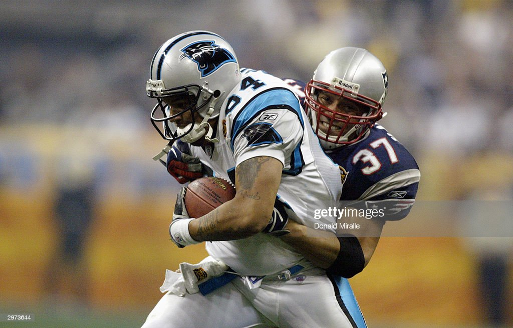 Tight end Jermaine Wiggins #84 of the Carolina Panthers is tackled by Rodney Harrison #37 of the New England Patriots during Super Bowl XXXVIII at Reliant Stadium on February 1, 2004 in Houston, Texas. The Patriots won 32-29 to claim their second Super Bowl in three years.