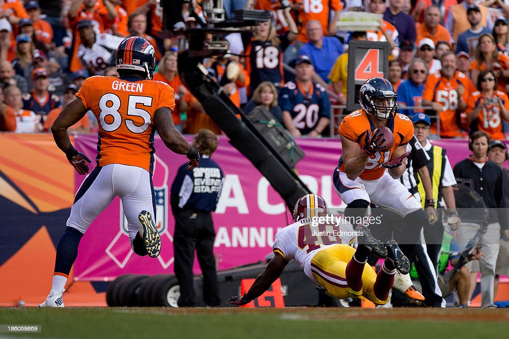 Tight end <a gi-track='captionPersonalityLinkClicked' href=/galleries/search?phrase=Joel+Dreessen&family=editorial&specificpeople=1611776 ng-click='$event.stopPropagation()'>Joel Dreessen</a> #81 of the Denver Broncos catches a pass for a touchdown during the fourth quarter as defensive back Jose Gumbs #48 of the Washington Redskins defends at Sports Authority Field Field at Mile High on October 27, 2013 in Denver, Colorado. The Broncos defeated the Redskins 45-21.