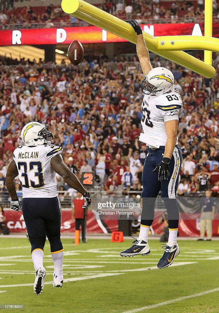 Tight end John Phillips #83 of the San Diego Chargers throws the football through the goal pose after scoring a 3 yard touchdown on a fumble recovery against the Arizona Cardinals during the preseason NFL game at the University of Phoenix Stadium on August 24, 2013 in Glendale, Arizona.