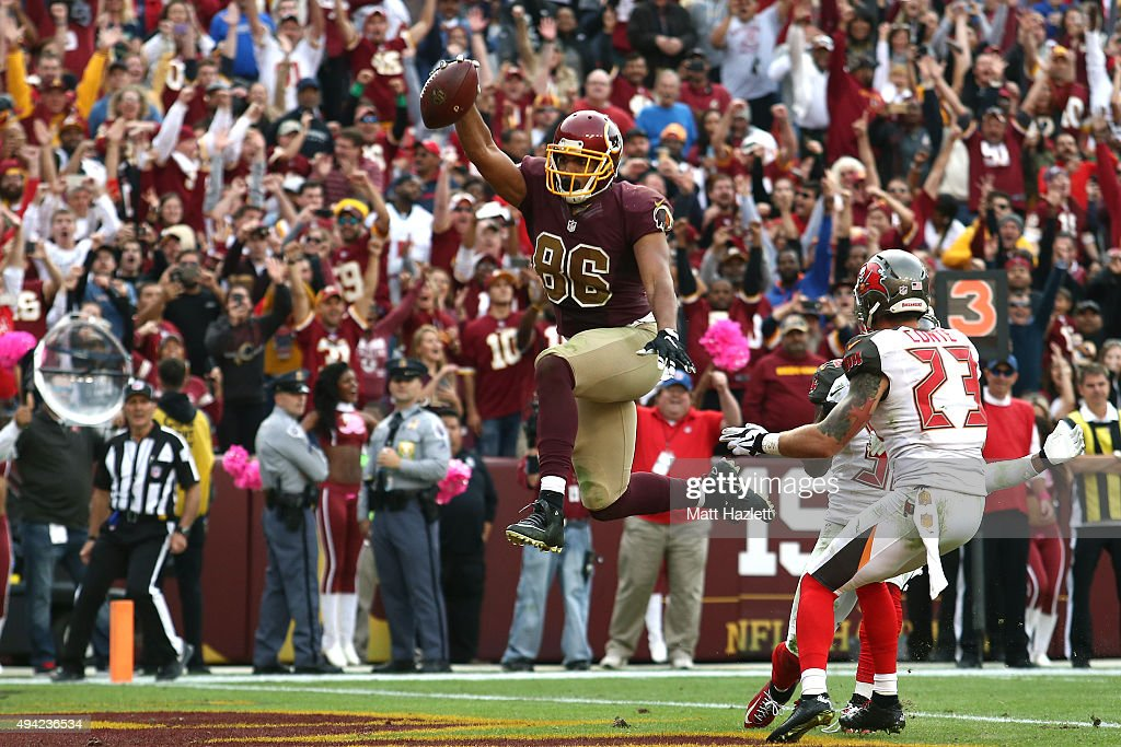 Tight end Jordan Reed #86 of the Washington Redskins scores a fourth quarter touchdown past strong safety Chris Conte #23 of the Tampa Bay Buccaneers during a game at FedExField on October 25, 2015 in Landover, Maryland.