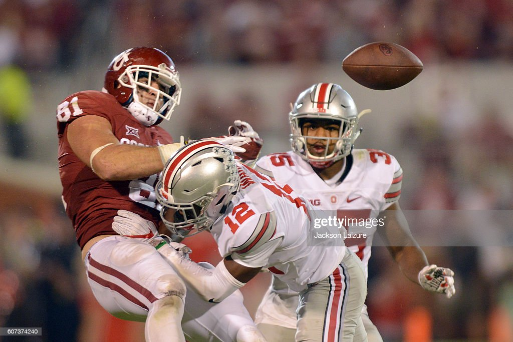 Tight end Mark Andrews #81 of the Oklahoma Sooners has the ball knocked out of his hands after getting hit by cornerback Denzel Ward #12 in front of linebacker Chris Worley #35 of the Ohio State Buckeyes on September 17, 2016 at Gaylord Family Oklahoma Memorial Stadium in Norman, Oklahoma.
