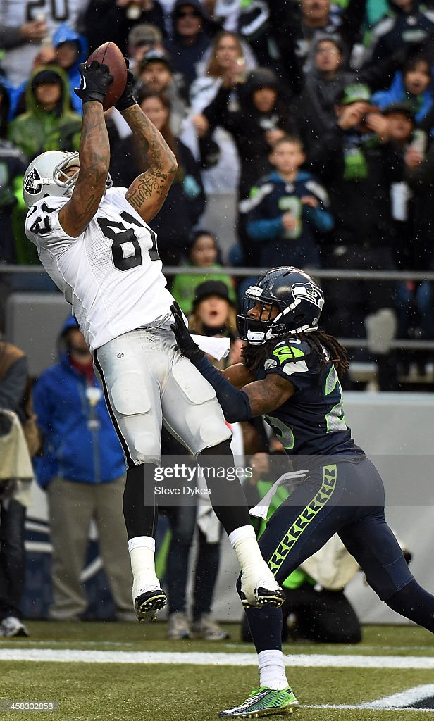 Tight end Mychal Rivera of the Oakland Raiders catches a touchdown in front of cornerback Richard Sherman of the Seattle Seahawks during the third...