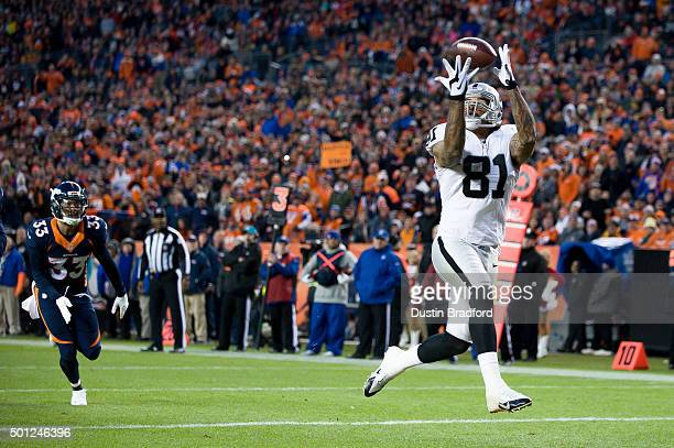 Tight end Mychal Rivera of the Oakland Raiders leaps and makes a 16 yard fourth quarter touchdown reception for at Sports Authority Field at Mile...