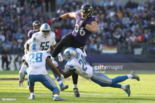Tight End Nick Boyle of the Baltimore Ravens leaps as he carries the ball over cornerback Nevin Lawson of the Detroit Lions in the first quarter...