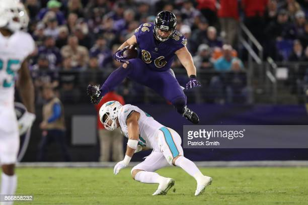 Tight End Nick Boyle of the Baltimore Ravens leaps over middle linebacker Kiko Alonso of the Miami Dolphins in the second quarter at MT Bank Stadium...