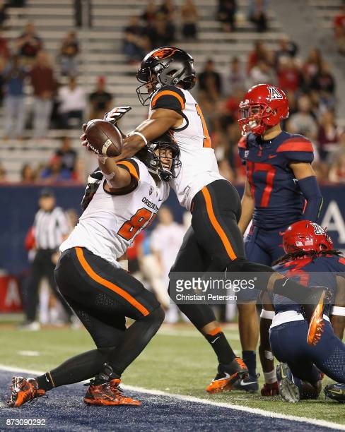 Tight end Noah Togiai of the Oregon State Beavers celebrates with wide receiver Jordan Villamin after Togiai scored on a 15 yard reception against...