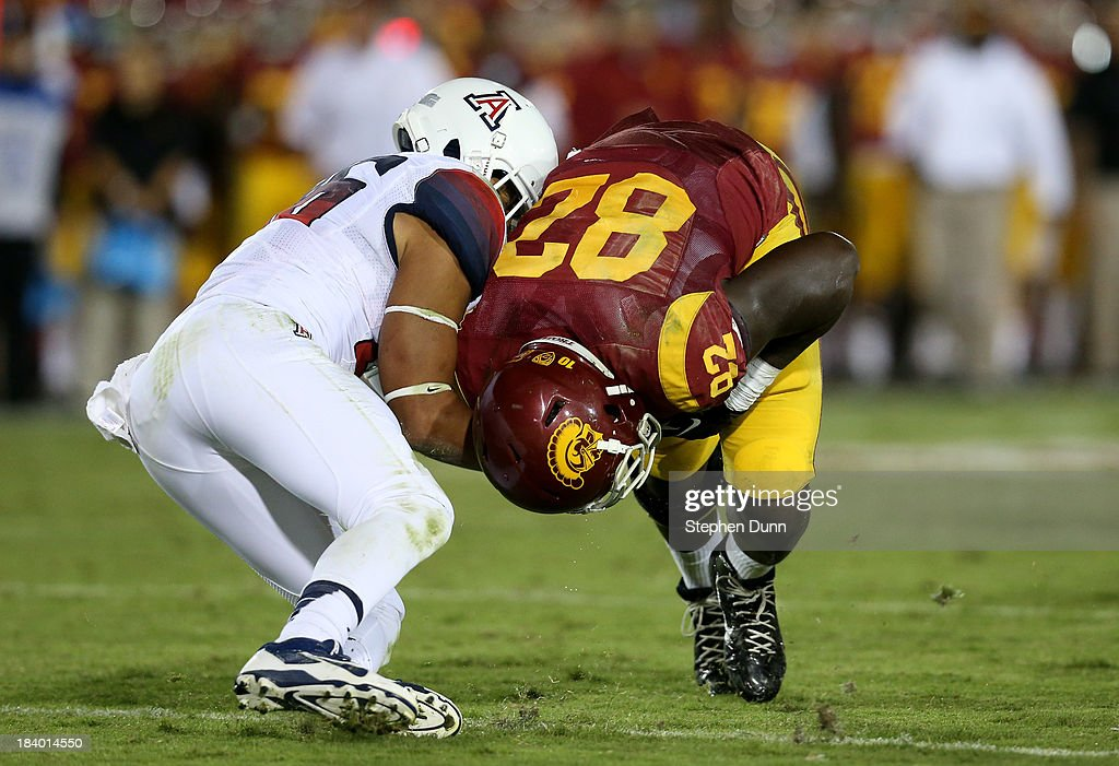 Tight end Randall Telfer #82 of the USC Trojans is tackled by safety Jourdon Grandon #26 of the Arizona Wildcats at Los Angeles Coliseum on October 10, 2013 in Los Angeles, California. USC won 38-31.