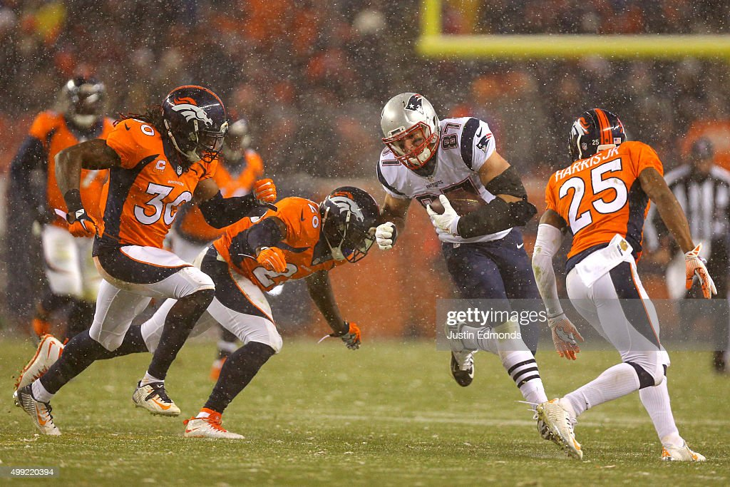 Tight end <a gi-track='captionPersonalityLinkClicked' href=/galleries/search?phrase=Rob+Gronkowski&family=editorial&specificpeople=5534525 ng-click='$event.stopPropagation()'>Rob Gronkowski</a> #87 of the New England Patriots carries the ball against free safety <a gi-track='captionPersonalityLinkClicked' href=/galleries/search?phrase=Darian+Stewart&family=editorial&specificpeople=4542671 ng-click='$event.stopPropagation()'>Darian Stewart</a> #26 of the Denver Broncos, strong safety <a gi-track='captionPersonalityLinkClicked' href=/galleries/search?phrase=David+Bruton&family=editorial&specificpeople=4023057 ng-click='$event.stopPropagation()'>David Bruton</a> #30 of the Denver Broncos, and cornerback <a gi-track='captionPersonalityLinkClicked' href=/galleries/search?phrase=Chris+Harris+-+American+Football+Cornerback&family=editorial&specificpeople=15029474 ng-click='$event.stopPropagation()'>Chris Harris</a> #25 of the Denver Broncos in the third quarter at Sports Authority Field at Mile High on November 29, 2015 in Denver, Colorado.