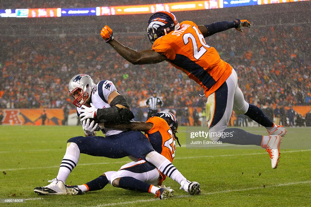 Tight end Rob Gronkowski #87 of the New England Patriots is tackled by free safety Bradley Roby #29 of the Denver Broncos and hit by free safety Darian Stewart #26 of the Denver Broncos in the first quarter at Sports Authority Field at Mile High on November 29, 2015 in Denver, Colorado.