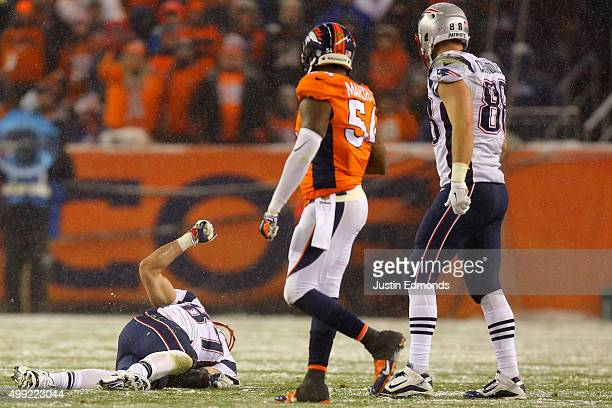 Tight end Rob Gronkowski of the New England Patriots lies on the field injured while inside linebacker Brandon Marshall of the Denver Broncos and...