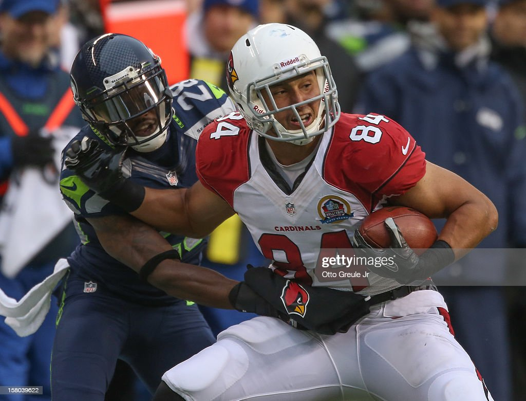 Tight end Rob Housler #84 of the Arizona Cardinals is tackled by cornerback Walter Thurmond #28 of the Seattle Seahawks at CenturyLink Field on December 9, 2012 in Seattle, Washington. The Seahawks defeated the Cardinals 58-0.