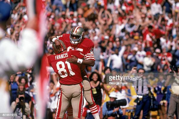 Tight end Russ Francis congratulates teammate wide receiver Mike Wilson of the San Francisco 49ers after scoring a touchdown against the Atlanta...