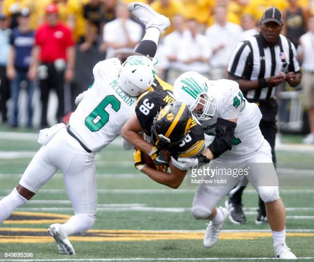 Tight end TJ Hockenson of the Iowa Hawkeyes is wrapped up during the second quarter by safety Kishawn McClain and linebacker Colton McDonald of the...