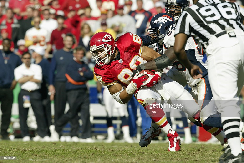 Tight end Tony Gonzalez of the Kanses City Chiefs get tackled by Linebacker Al Wilson of the Denver Broncos during the NFL game on October 20 2002 at...