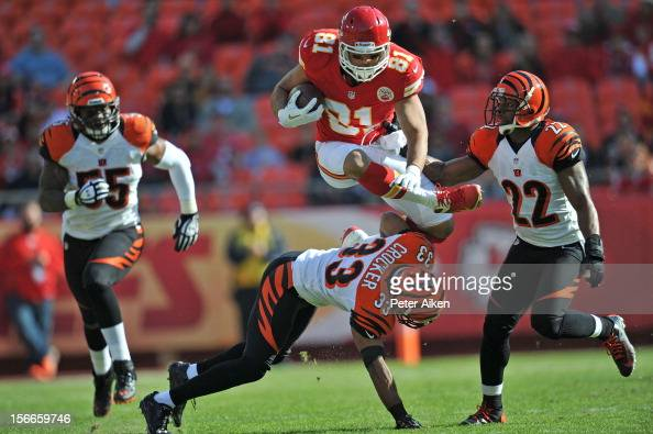 Tight end Tony Moeaki of the of the Kansas City Chiefs leaps over defenders Chris Crocker and Nate Clements of the Cincinnati Bengals in route to a...