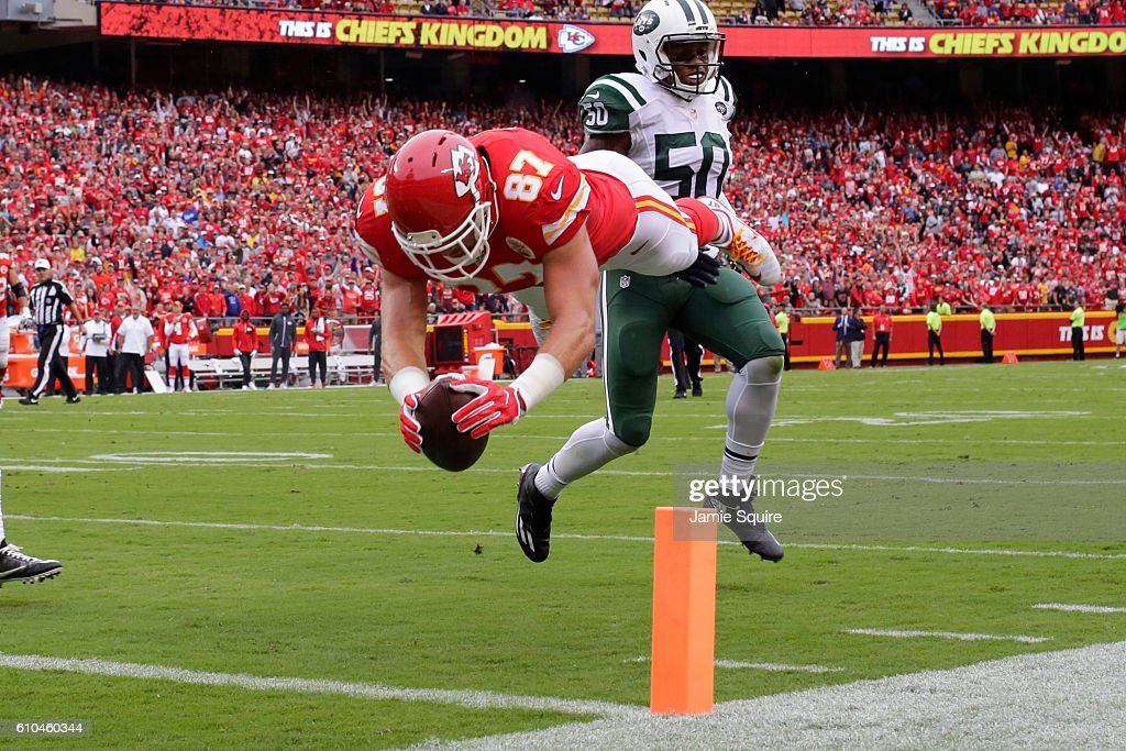 Tight end Travis Kelce #87 of the Kansas City Chiefs dives in to the end zone to score the games first touchdown in front of cornerback Marcus Williams #20 of the New York Jets at Arrowhead Stadium during the first quarter of the game on September 25, 2016 in Kansas City, Missouri.