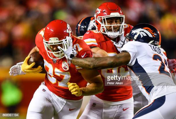 Tight end Travis Kelce of the Kansas City Chiefs fights through the tackle attempt of cornerback Aqib Talib of the Denver Broncos during the first...