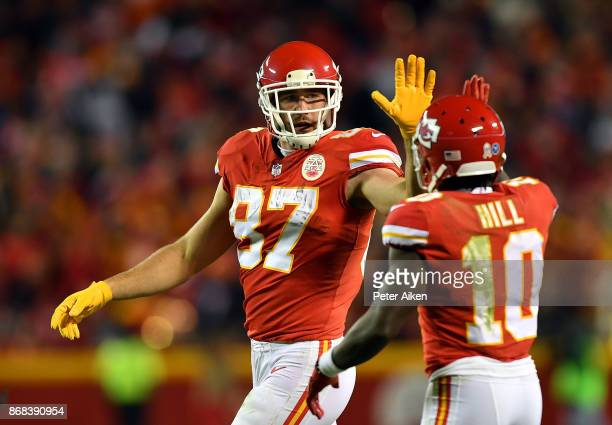 Tight end Travis Kelce of the Kansas City Chiefs highfives wide receiver Tyreek Hill during the game against the Denver Broncos at Arrowhead Stadium...