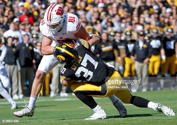 Tight end Troy Fumagalli of the Wisconsin Badgers battles to the end zone during the second quarter against defensive back Brandon Snyder of the Iowa...