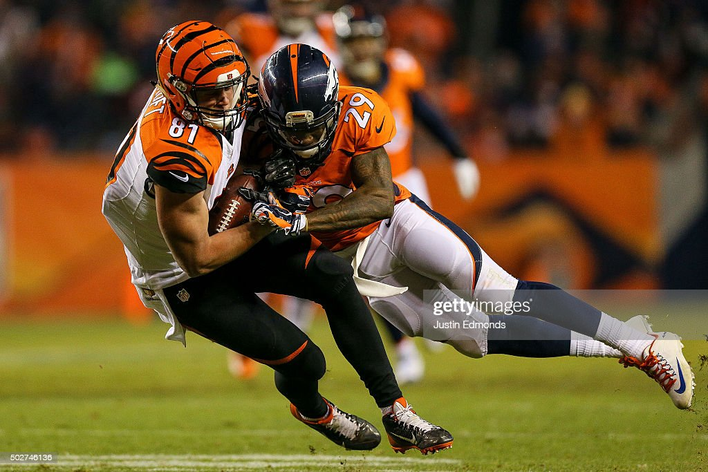 Tight end Tyler Kroft #81 of the Cincinnati Bengals is tackled by free safety Bradley Roby #29 of the Denver Broncos after a 12 yard reception in the second quarter of a game at Sports Authority Field at Mile High on December 28, 2015 in Denver, Colorado.