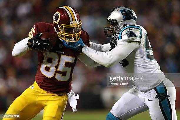 Tight end Vernon Davis of the Washington Redskins carries the ball against outside linebacker Thomas Davis of the Carolina Panthers in the third...