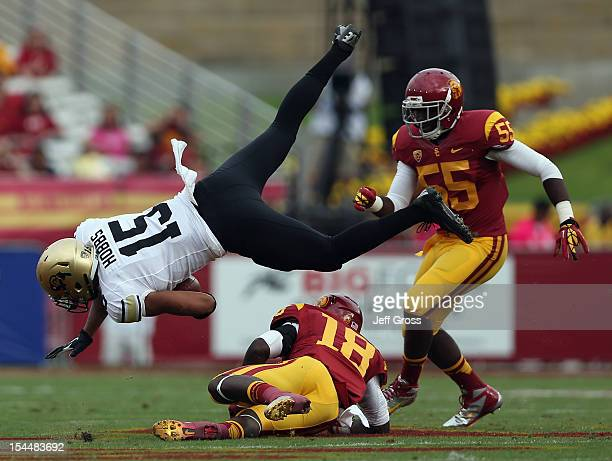 Tight end Vincent Hobbs of the Colorado Buffaloes is tripped up by linebacker Dion Bailey of the USC Trojans as Lamar Dawson of the Trojans pursues...