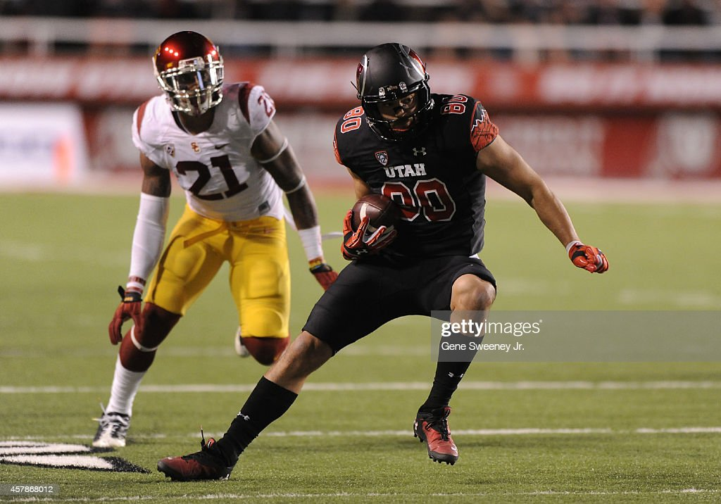 Tight end Westlee Tonga of the Utah Utes runs for a first down while being defended by Su'a Cravens of the USC Trojans at RiceEccles Stadium on...