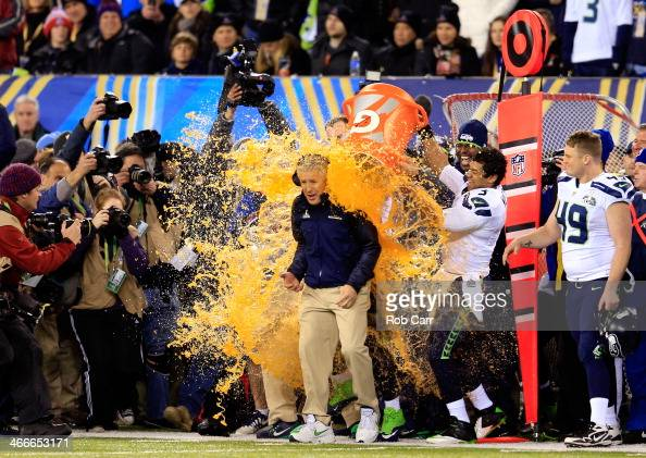 Tight end Zach Miller and quarterback Russell Wilson of the Seattle Seahawks dump Gatorade on head coach Pete Carroll in the fourth quarter of Super...