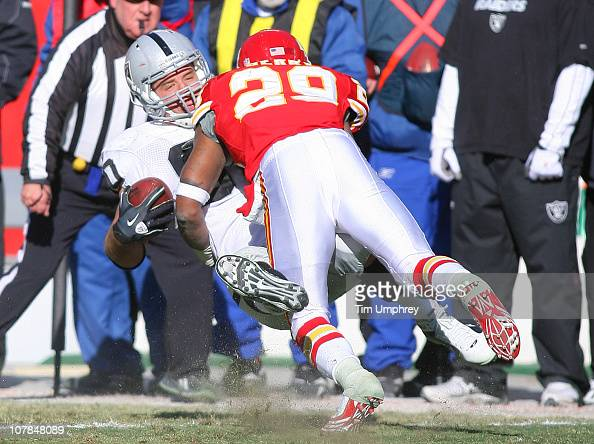Tight end Zach Miller of the Oakland Raiders is tackled by safety Eric Berry of the Kansas City Chiefs in a game at Arrowhead Stadium on January 2...