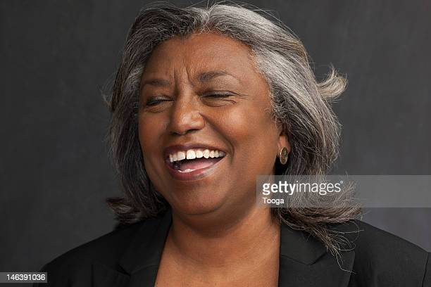 Tight portrait of senior laughing with closed eyes