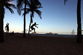 Tight rope walkers or slackliners silhouetted against the late afternoon sky practice at Ipanema beach Slackline is a modern version of the tightrope...