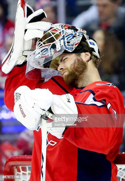 Tight squeeze for Washington Capitals goalie Braden Holtby as he replaces his helmet during a NHL game between the Washington Capitals and the...
