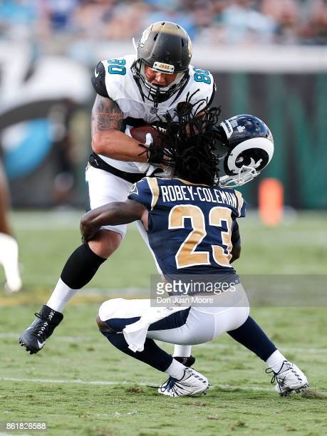 Tightend James O'Shaughnessy of the Jacksonville Jaguars forces the helmet off the head of Cornerback Nickell RobeyColeman of the Los Angeles Rams...