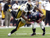 Tightend Owen Daniels of the Houston Texans is tackled by linebacker Larry Foote and linebacker LaMarr Woodley of the Pittsburgh Steelers in the...