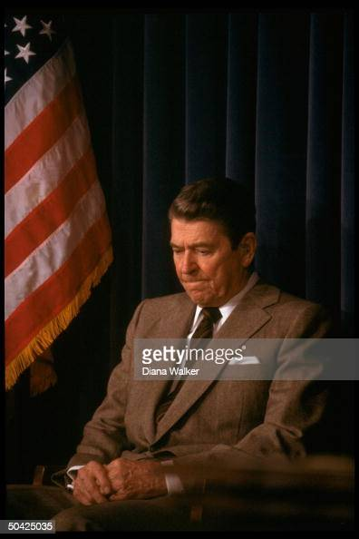 Tightlipped downcast Pres Reagan sitting lost in thought at WH