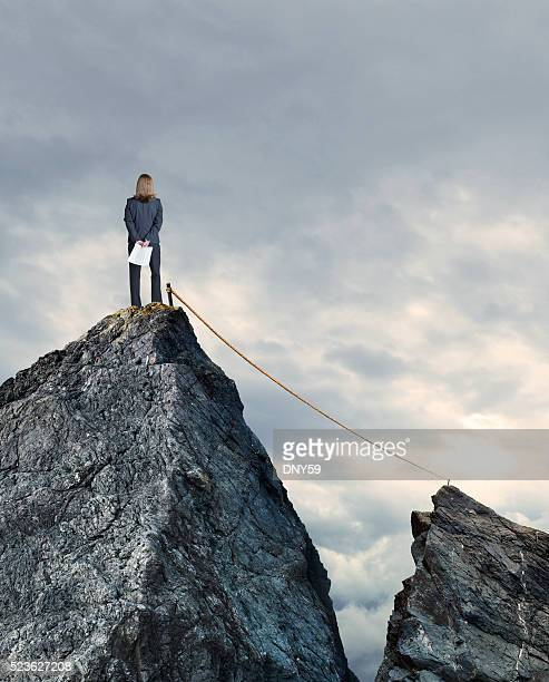 Tightrope Connecting Two Mountain Tops As Bunesswoman Looks On