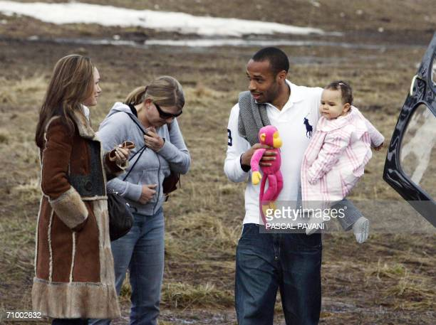 French forward Thierry Henry speaks with his wife Nicole Merry as he holds his daughter Tea upon his arrival for the French national football team's...