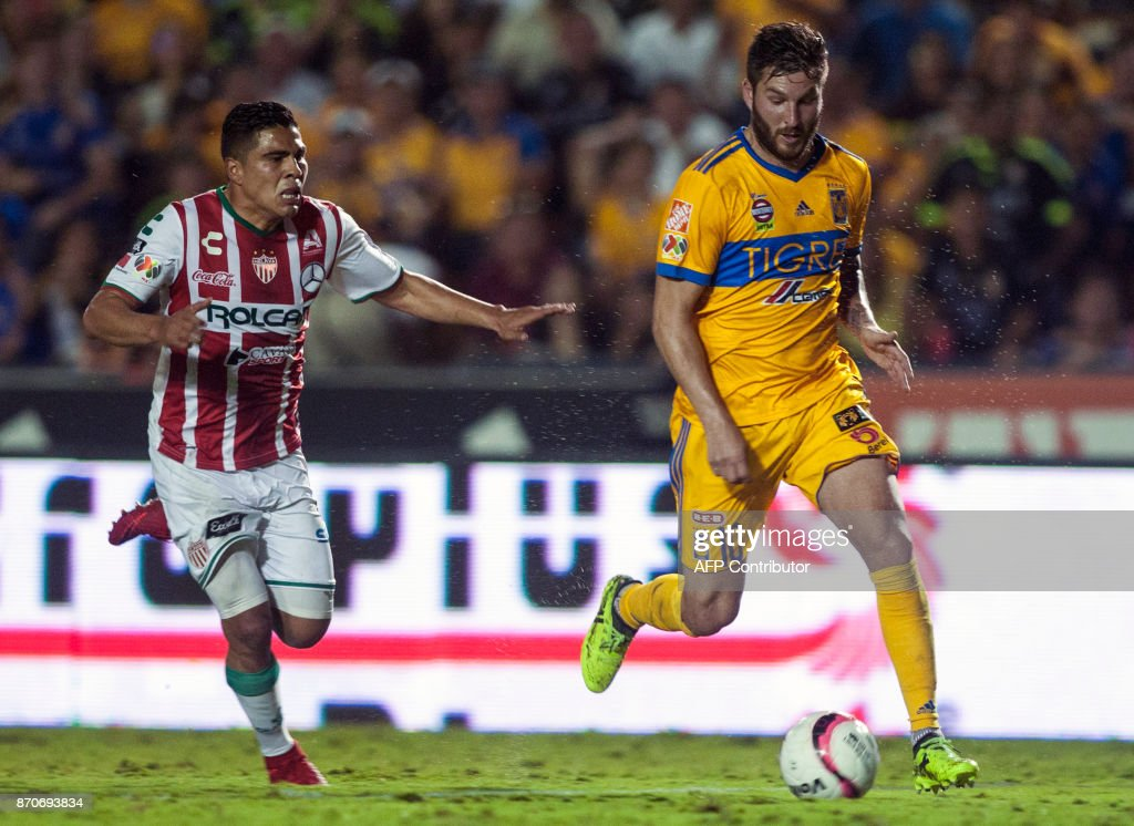 Tigres' Andre Pierre Gignac (R) vies for the ball with Necaxa's Luis Perez (L)during the 2017 Mexican Apertura tournament football match, at Universitario stadium in Monterrey, Mexico on November 5, 2017. /