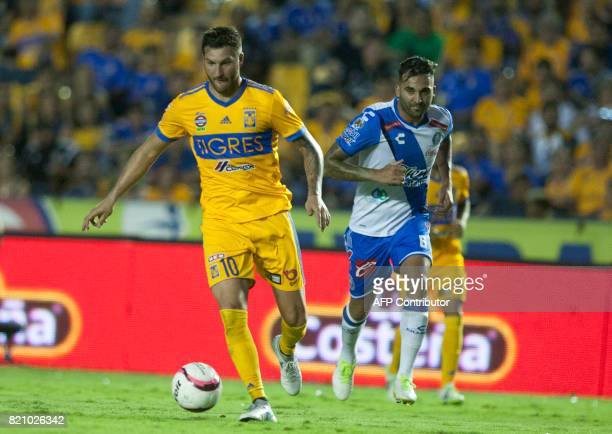 Tigres' French footballer AndrePierre Gignac drives the ball past Pablo Miguez of Puebla during their Mexican Apertura football tournament match at...