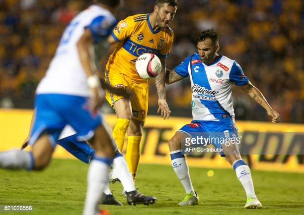 Tigres' French footballer AndrePierre Gignac vies for the ball with Pablo Miguez during their Mexican Apertura football tournament match at the...