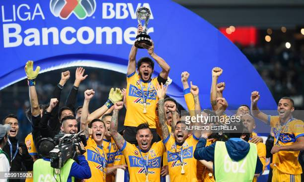 Tigres players celebrate their victory as they rise the trophy after winning the Mexican Apertura 2017 football tournament final match against...