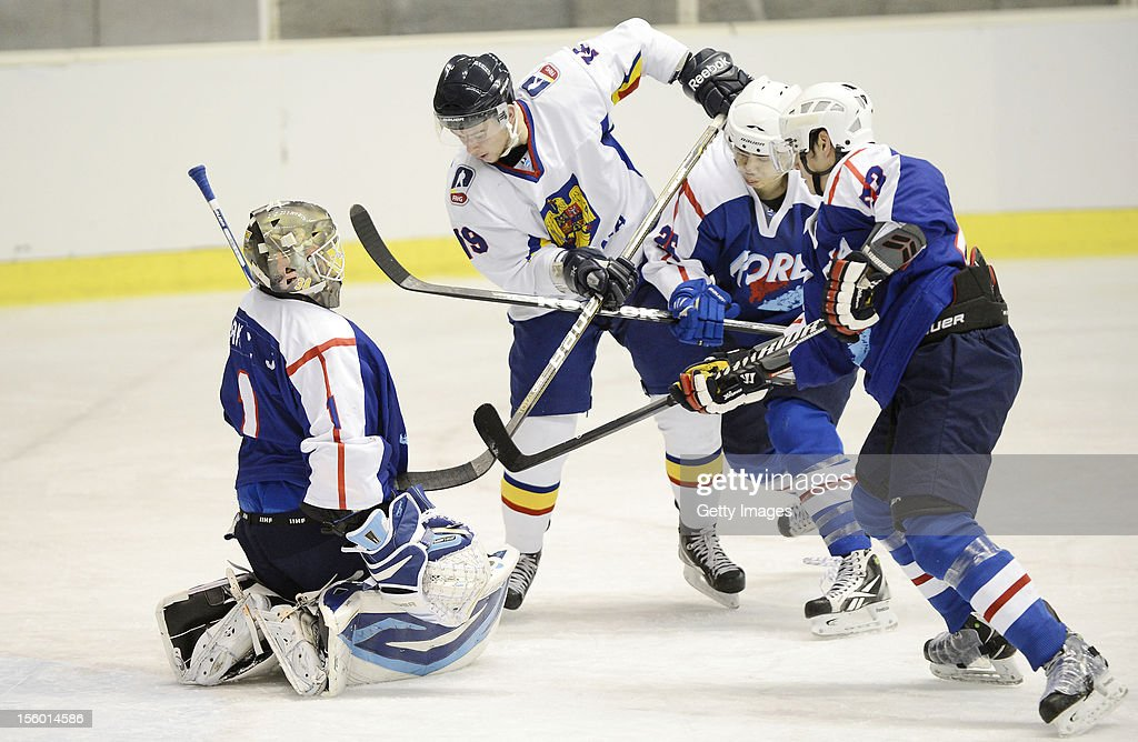Tihamer Becze #19 of Romania skates against Park Sungie (1L) #1, Park Woosang (2R) #26 and Oh Hyonho #23 of South Korea during the Ice Hockey Sochi Olympic Pre-Qualification Group J match between South Korea and Romania at Nikko Kirifuri Ice Arena on November 11, 2012 in Nikko, Tochigi, Japan. South Korea won 2-0.