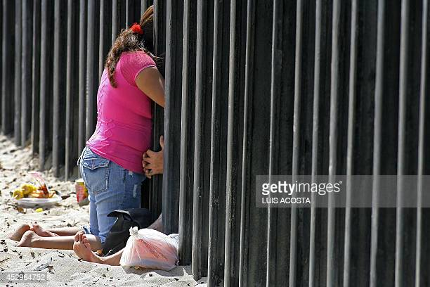 STORY 'Tijuana A City Under the Shadow of a Double Wall' A Mexican couple shares a moment through the fence that separates the United States from...