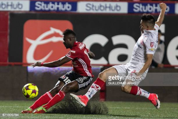 Tijuana's Aviles Hurtado vies for the ball with Toluca`s Efrain Velarde during their Mexican Clausura 2017 Tournament football match at the Caliente...
