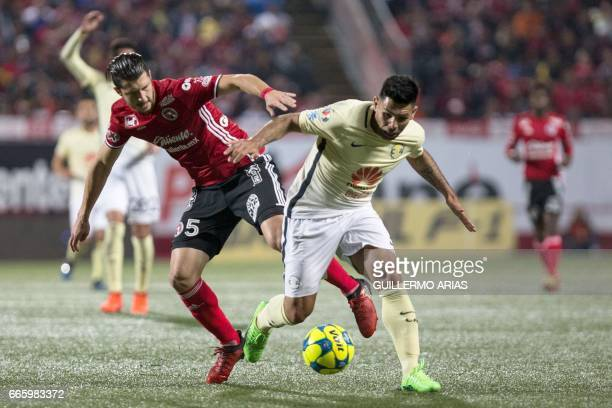 Tijuana's Guido Rodriguez vies for the ball with America's Silvio Romero during their Mexican Clausura 2017 Tournament football match at the Caliente...