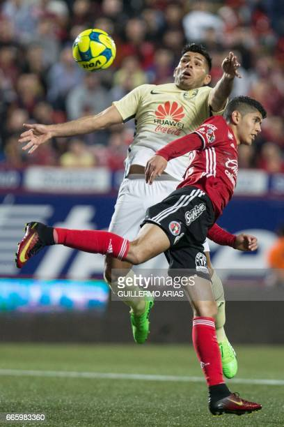 Tijuana's Joe Corona vies for the ball with America's Silvio Romero during their Mexican Clausura 2017 Tournament football match at the Caliente...