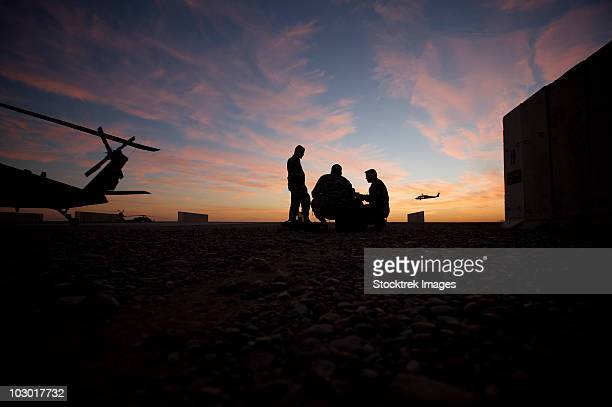 Tikrit, Iraq - A UH-60 Black Hawk crew carry out a mission brief at sunset.