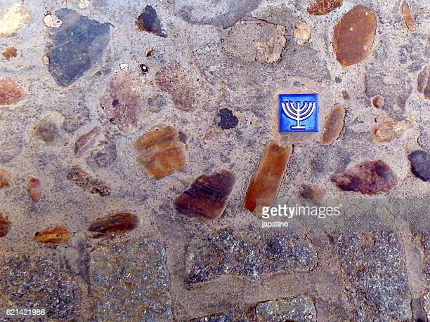 Tile embedded in the ground with the Jewish symbol of Menorah